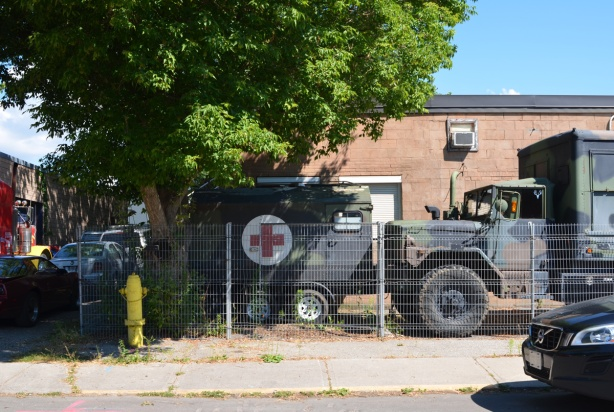 old drab green military truck and ambulance with red cross symbol parked in front of a building