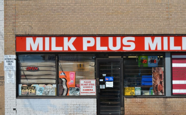 Milk plus convenience store with bright red and white sign saying milk plus milk plus. sign in window that says please do not steal