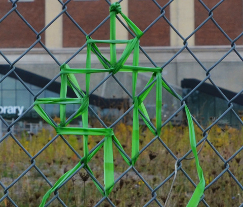 green ribbon woven into the chainlink fence between the West Toronto Railpath and MOCA, the Museum of Contemporary Art