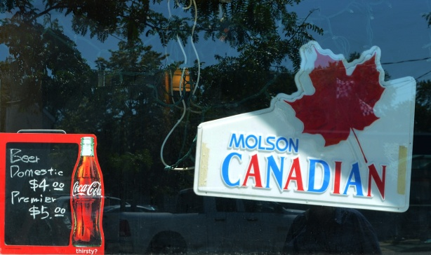 bar window, with Molson Canadian advert with red maple leaf, also coca cola sign with beer prices listed