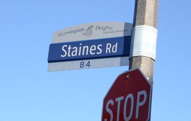 Blue and white Toronto street sign for Staines Rd, top part is sign for Morningside Heights, naturally beautiful