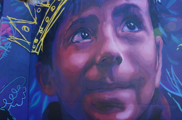 part of a mural, a large face of a boy in pinks and blues, with a yellow crown drawn on top of his head