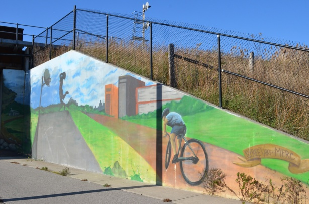 old mural on concrete wall, of a person on a bike on a path, someone playing basketball, in the mural,