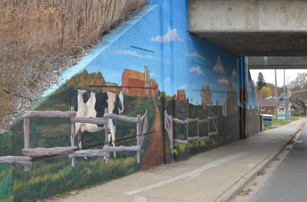 cow, farmyard scene in a mural, beside sidewalk on railway underpass