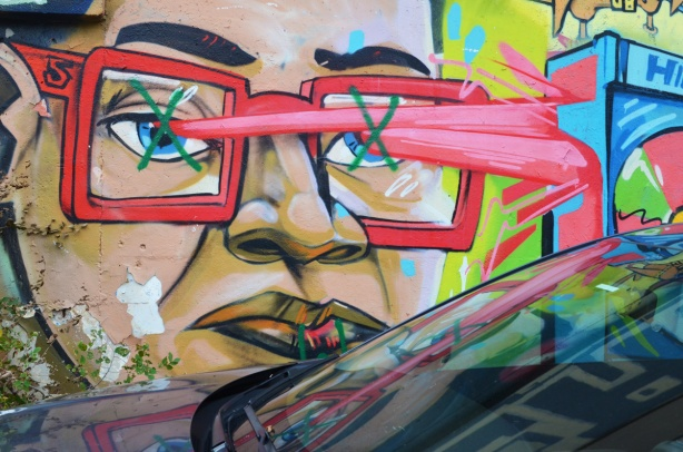 part of a uber5000 mural of a person wearing red glasses, also reflected in the windshield of the car that is parked beside the wall