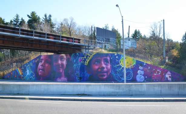 a mural with three large kids faces in purples, pinks, and blues,
