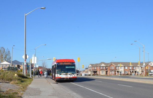 TTC bus parked on Finch just west of Morningside, route 133 Neilson. A row of houses in the background, on Morningside