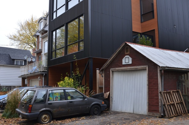 old car and old garage in front of a large new modern house