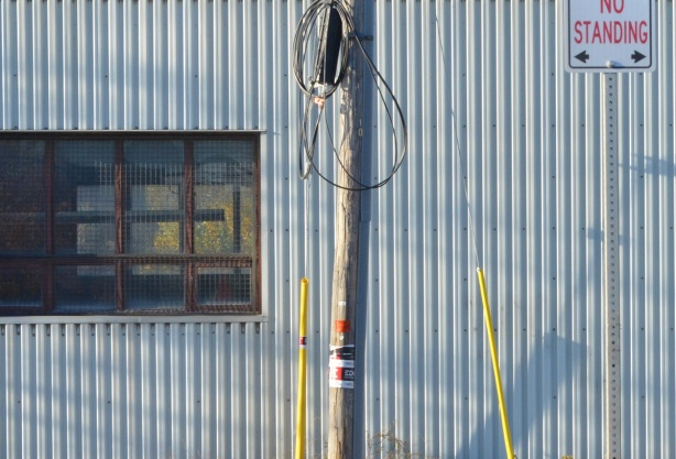 a grey utility pole and a small pole with a no standing sign in front of a light grey metal building with a window in it