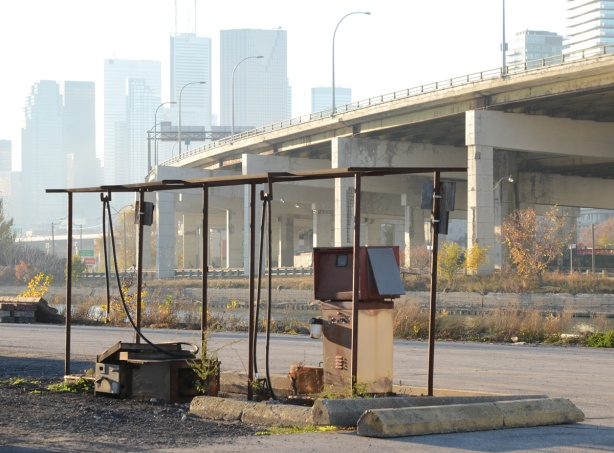 old gas pump at now abandoned marine gas station beside the Keating channel, Gardiner Expressway, CN Tower and Toronto skyline in the distance
