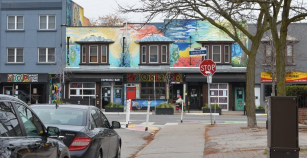 row of stores and cafes on Danforth, covered with street art, the Only Cafe,