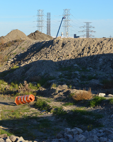 hydro poles and wires in the distance, piles of dirt in the foreground