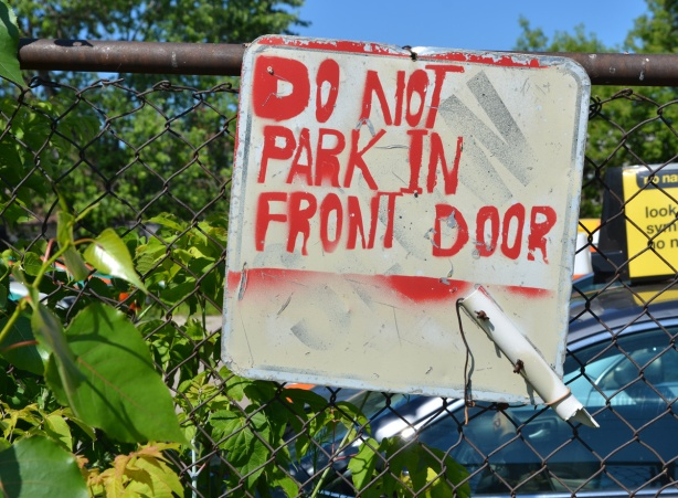 hand painted sign on a chain link gate that says do not park in front door