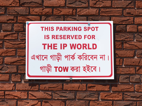 no parking sign on a brick wall, partially in english and partially in another language with a different alphabet