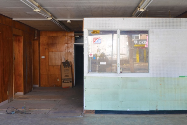 looking through the window of an empty store, pegboard, interior window, and wood paneling on some walls