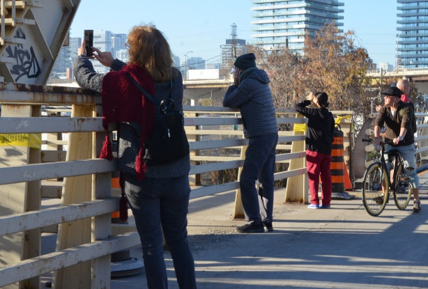 people standing on the cherry street bridge taking pictures of the new bridge