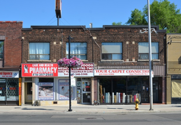 old two storey brick building on Danforth, stores, pharmacy, walk in clinic, and carpet store, your carpet connection with rolls of carpet in the window