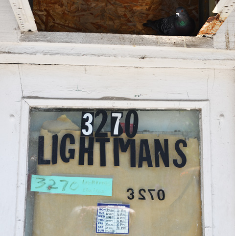 a pigeon has found a place to sit on a broken opening above a door to lightmans store, glass door with brown paper covering it, white wood frame, painted, number 3270 in different colours