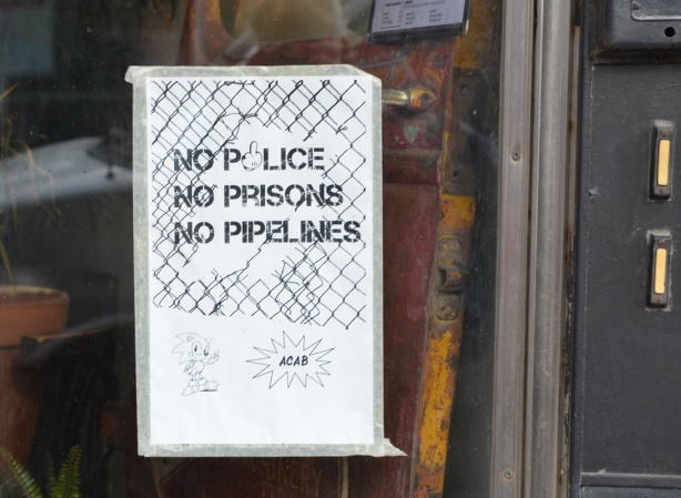 no police, no prisons, no pipeline, poster on a glass door