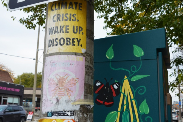 2 posters on a utility pole plus a painted street box behind. One poster says climate crisis wake up disobey. The other poster has a pink bee