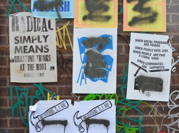 posters on a wall, many have been spray painted over