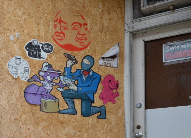 paper paste ups on a plywood board covering a window beside door on abandoned building, Closed sign still on door