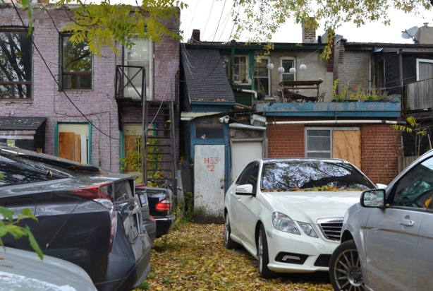 used cars parked behind two empty buildings
