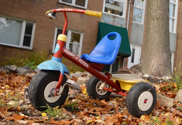 a radio flyer tricycle parked on the grass, with lots of fallen leaves, in front of brick apartment building