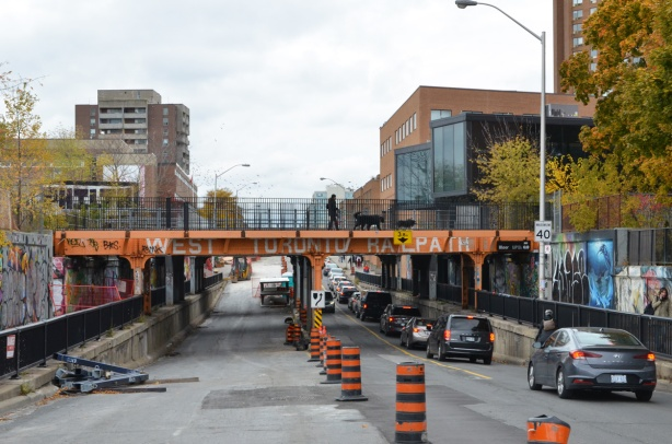 railway bridge over Bloor West near Dundas, painted orange, construction on one side of the road so traffic diverted to the other side