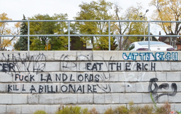 words scrawled on a concrete wall by a parking lot. eat the rich, kill a billionaire, fuck landlords,