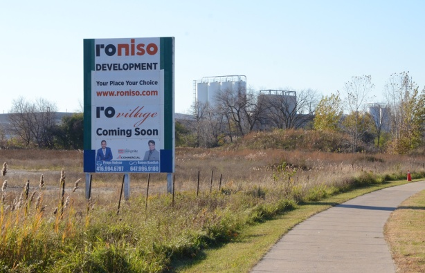 billboard advertisement for development property on vacant land, rovillage coming soon it says