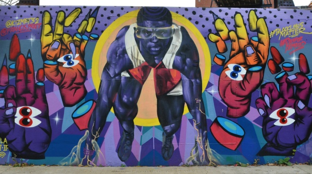 mural of a black man in the stance held at the beginning of a running race,