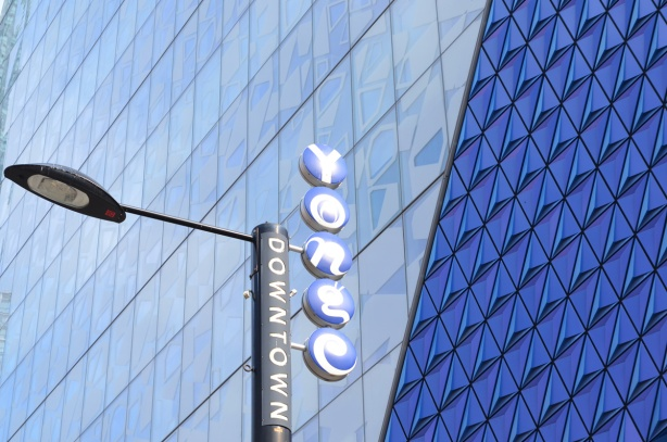 blue glass on the exterior of Ryerson student building, with a downtown yonge sign on a street light beside the building