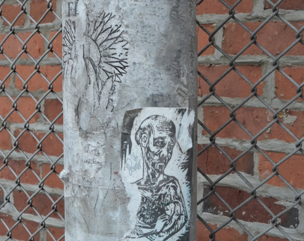 paper pasteup on a metal pole, sad man
