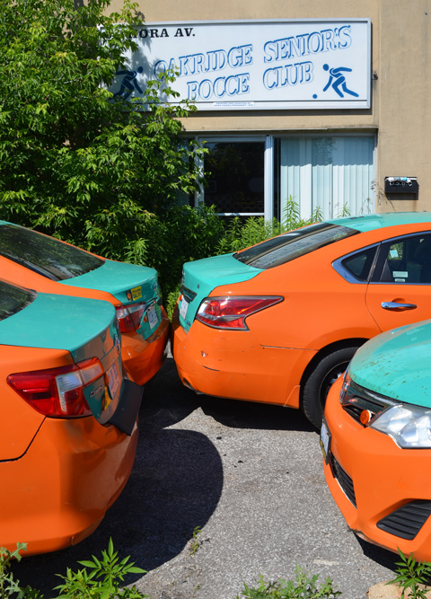 four orange and green taxis parked in front of a building that has a sign that says Oakridge Seniors Bocce Club