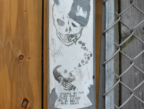 paper pasteup on a metal pole, top is a skull looking down, bottom is a man looking up, with words