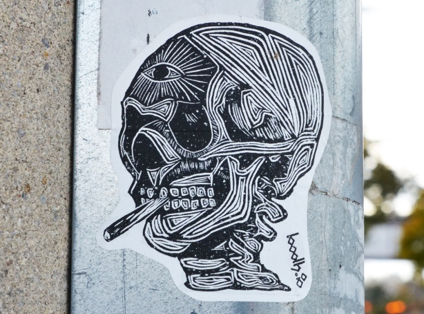 sticker graffiti of a head without the skin, showing eye socket, muscles, teeth, top vertebrae, smoking a cigarette