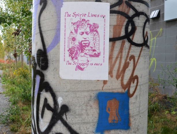 pink and white poster on a pole, along with a stencil graffiti of a cold coloured torso on blue background