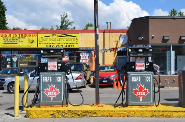 gas station, two pumps, star self service gas, cars parked behind at auto mechanic shop, top quality auto and cars r us toronto, open sign