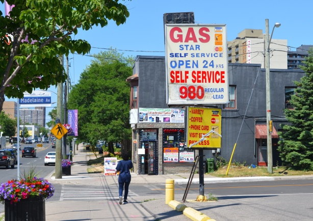 woman walking on Danforth at Madeleine, past star self service gas station, large sign with price of gas as 98 cents a litre, computer store on opposite side of street