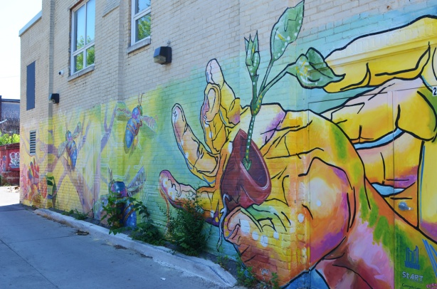 mural of a hand holding a plant growing in a flower pot, plus bees,