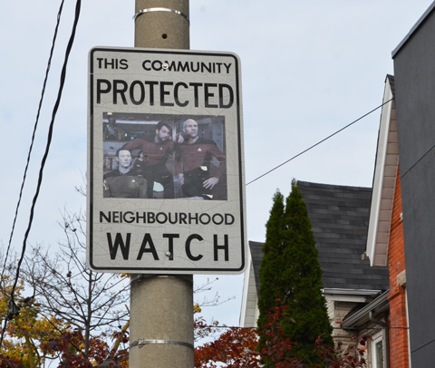 neighbourhood watch street sign with added picture of three characters from Star Trek