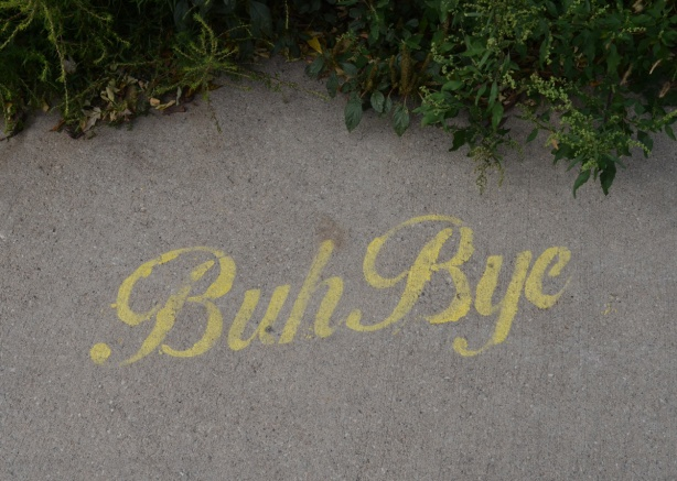 yellow stencil graffiti on sidewalk, words that say buh bye