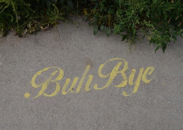 yellow stencil graffiti on sidewalk, words that say buh bye