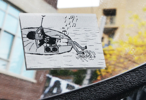 small sticker of a black drawing of a man floating on somethings round in the water, with 416 on his T shirt, his feet in the water, a ghetto blaster beside him