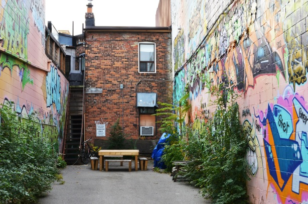 back of two storey brick building with a small paved space behind it, a table and benches are near the building, street art on both sides of the small space (the buildings on either sode)