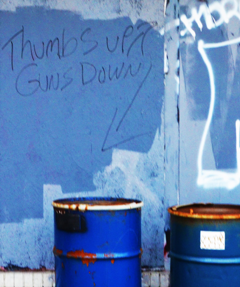 old blue oil drums beside a blue wall with graffiti words that say thumbs up and guns down
