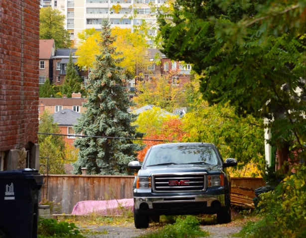 a G M C truck is parked in a gravel driveway between two buildings, in the background is a couple of rows of houses and a tall apartment building behind that