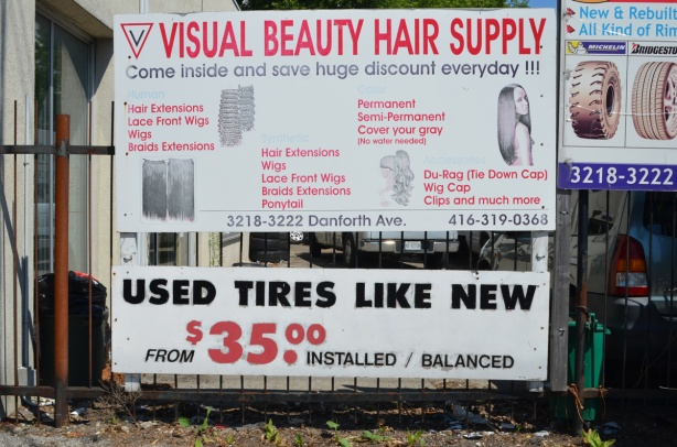 on a fence beside a store, advertising used tires for sale , like new, at thirty five dollars each. also a sign for visual beauty hair supply with a list of some of their products