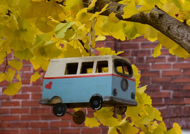 a small replica of a VW bus hanging from a tree. bus is painted white and blue and has a red heart on it